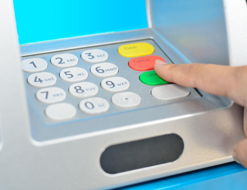 Finger pressing enter. On ATM keyboard stock photo