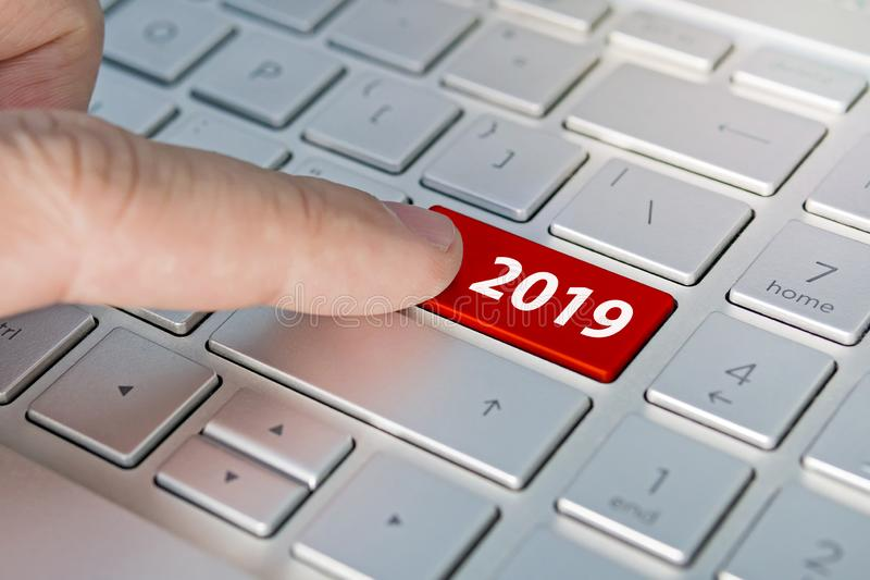 Finger pressing keyboard key written 2019 newyear. finger presses a button on the gray keyboard. Beginning of new year. royalty free stock images