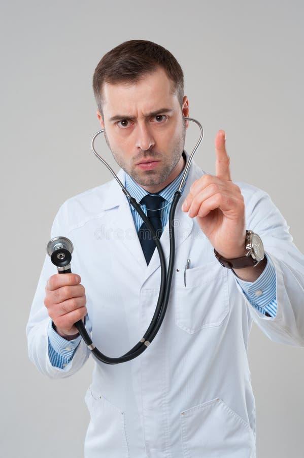 Finger punteagudo masculino del doctor para arriba con el estetoscopio imagen de archivo libre de regalías