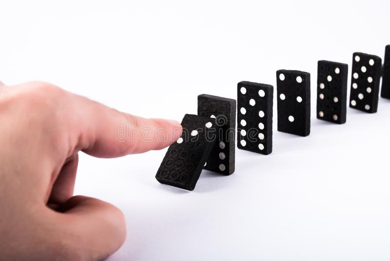 Finger push dominoes tiles and they fall isolated on a white background royalty free stock image