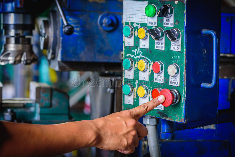 Finger push on red emergency stop switch milling machine. In factory workshop royalty free stock photos