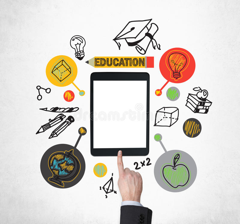 A finger is pushing the button on the tablet with blank screen. Educational icons are drawn around the tablet. A concept of education and technology stock photo