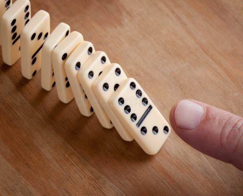 Finger que empuja pedazos del dominó fotos de archivo libres de regalías
