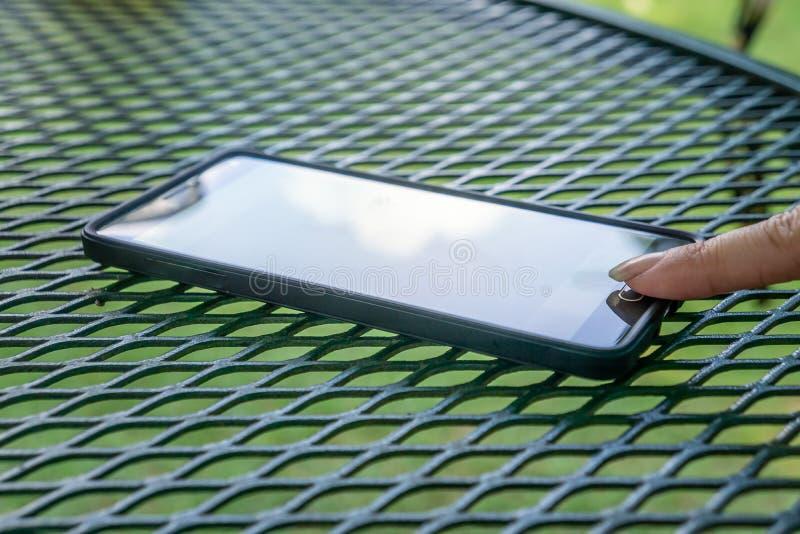 Finger que golpea ligeramente en del botón en el teléfono celular elegante Fuera de la reclinación sobre la tabla de patio fotografía de archivo