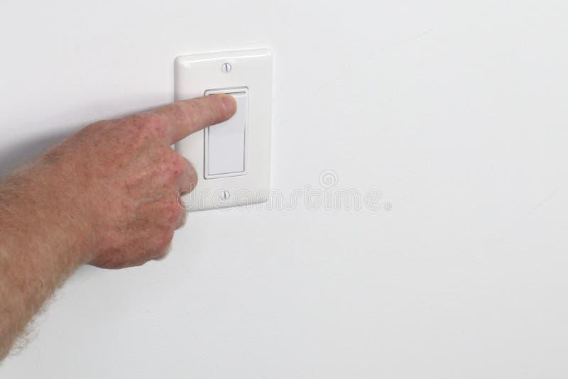 Finger que mueve de un tirón un interruptor de la luz blanco de la izquierda foto de archivo libre de regalías