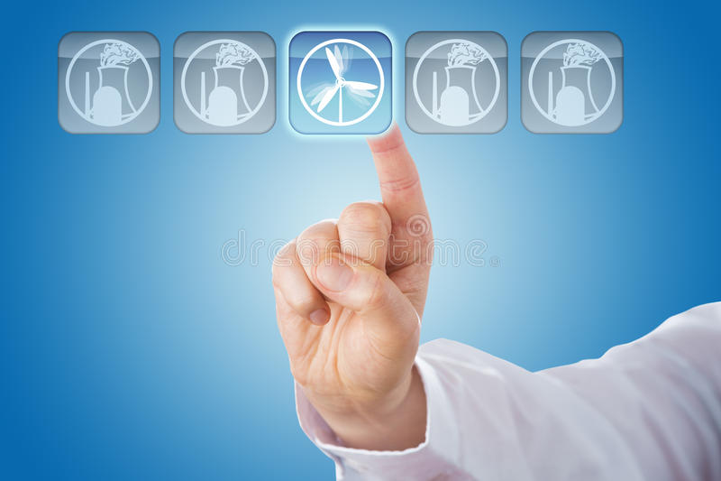 Finger que selecciona energía eólica entre iconos nucleares fotos de archivo