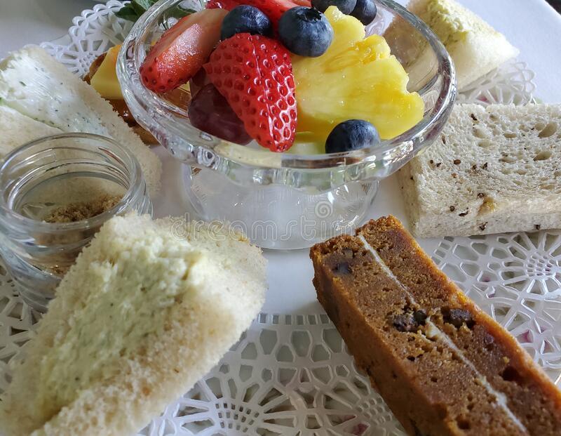 Finger sandwiches and fruit cup served on a doily royalty free stock photo