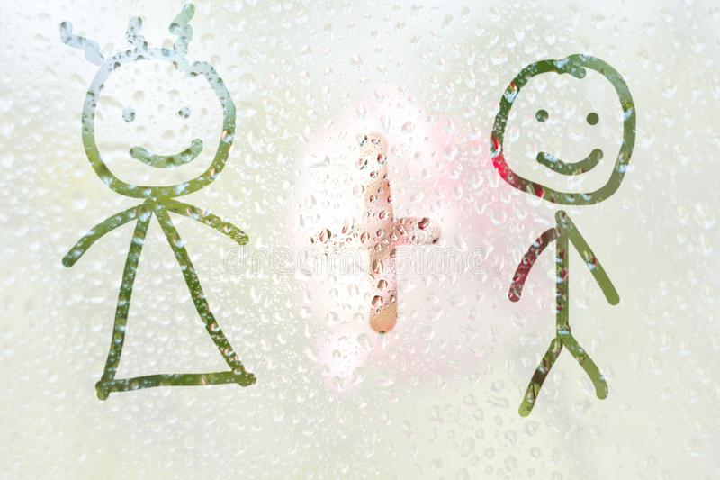 Finger-shaped drawing of the stripes of a boy and a girl on a translucent fogged glass. raindrops of spring rain on the window stock photos