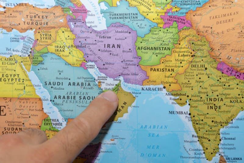 Finger som pekar till en f?rgrik lands?versikt av F?renadeen Arabemiraten Dubai i Mellan?sten p? golf royaltyfri foto