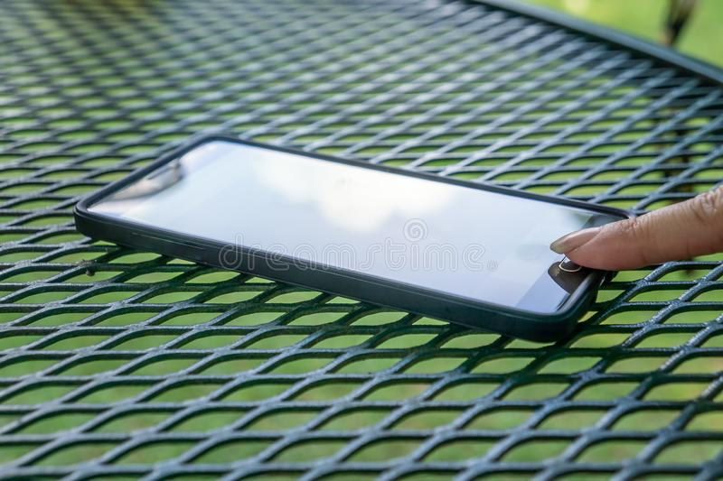 Finger tapping on off button on smart cell phone. Outside resting on patio table. Person`s finger tapping on touch button using smart cell phone. Modern tech stock photography