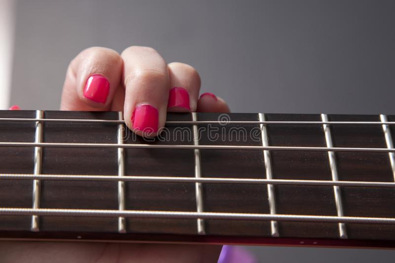 Finger on third fret. Hot pink fingernail on a bass guitar string stock image