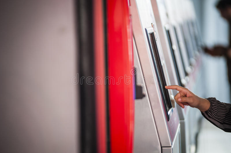Finger on touch screen. A lady's finger touching the ticket vending machine's touch screen stock image