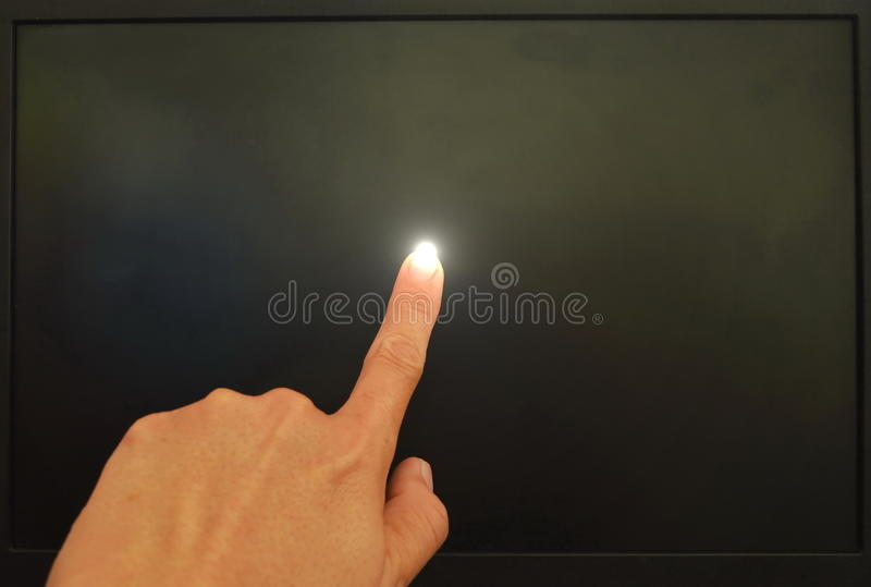 Finger touching on black computer screen and light on. Human finger touching on black computer screen and light on stock photography
