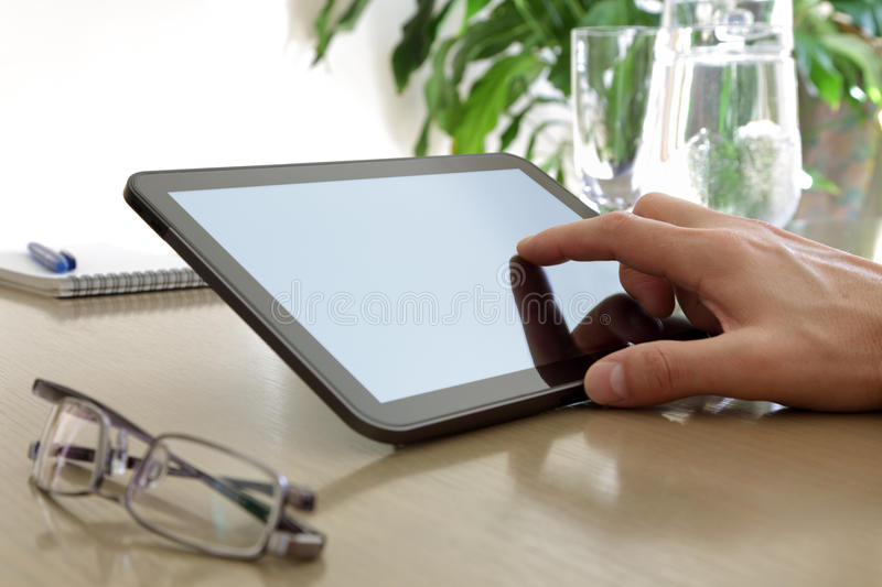 Finger touching screen of a digital tablet. Businessman in a meeting pointing to the screen of a tablet-pc stock photos