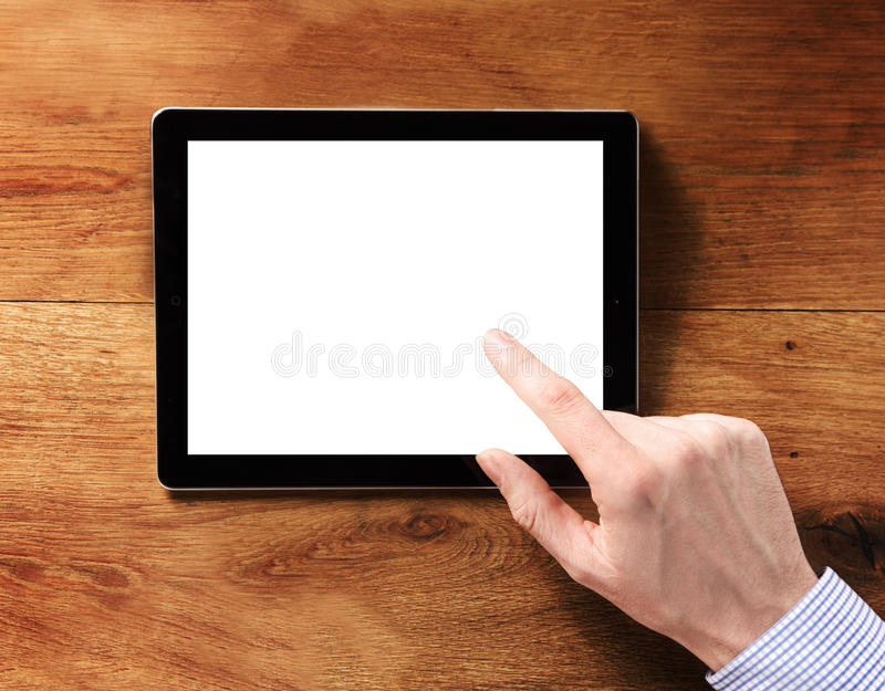Finger Touching White Tablet Computer Screen. Human Finger Touching Blank White Tablet Computer Screen, Emphasizing Copy Space, on Top of the Wooden Table royalty free stock photos