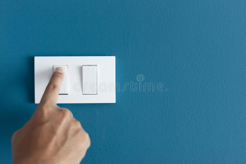 A finger turning on lighting switch on rough on blue dark wall. royalty free stock photography