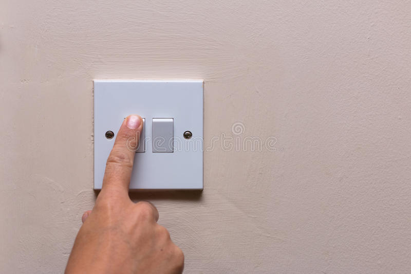 Finger turning off the light to save on consumption. And energy royalty free stock photo