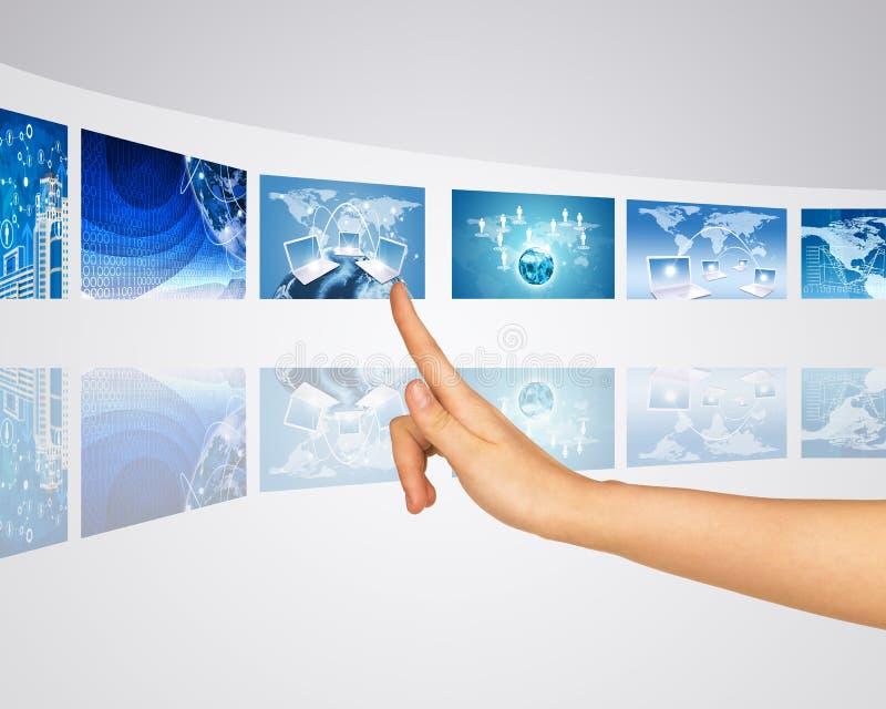 Finger wählt einen von virtuellen Schirmen vor stockfotografie