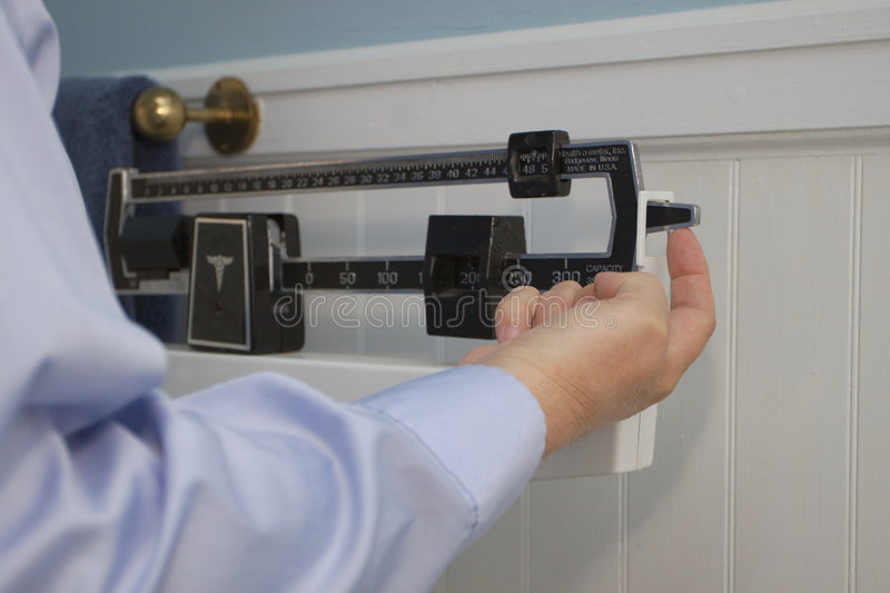 Finger on weight scale. Man's finger pushing up on a weight scale that is weighing too heavy royalty free stock photo
