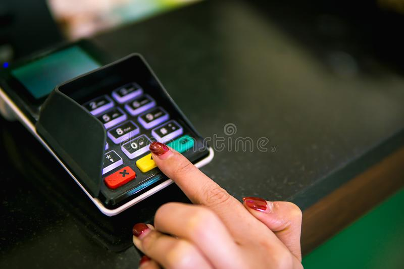 Finger of women inserting password or pin code on machine keypad of payment terminal royalty free stock image