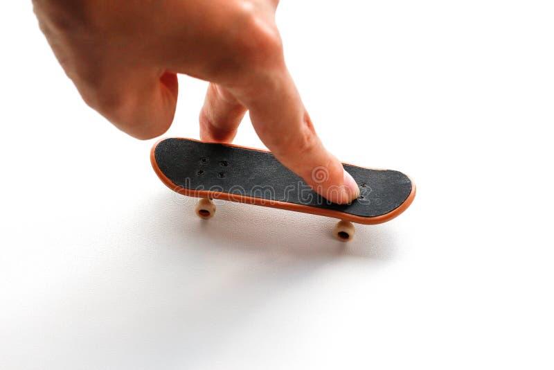 fingerboard Малый скейтборд и рука конец вверх белизна изолированная предпосылкой стоковые фото