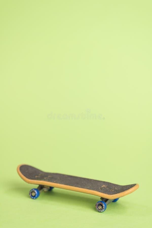 Fingerboard auf einem grünen Hintergrund in der Mitte stockfotos