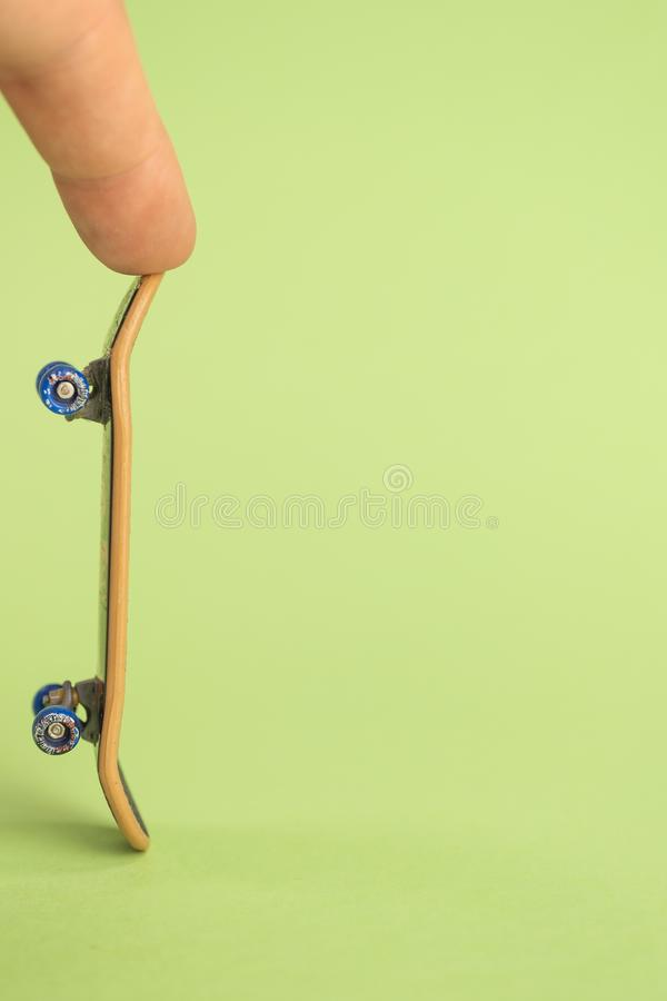 Fingerboard. Man hoplding by two fingers small skateboard on green background stock photography
