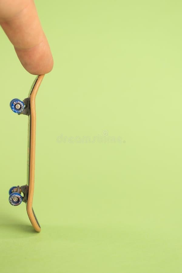 fingerboard Mann, der durch das kleine Skateboard mit zwei Fingern auf grünem Hintergrund hoplding ist stockfotografie