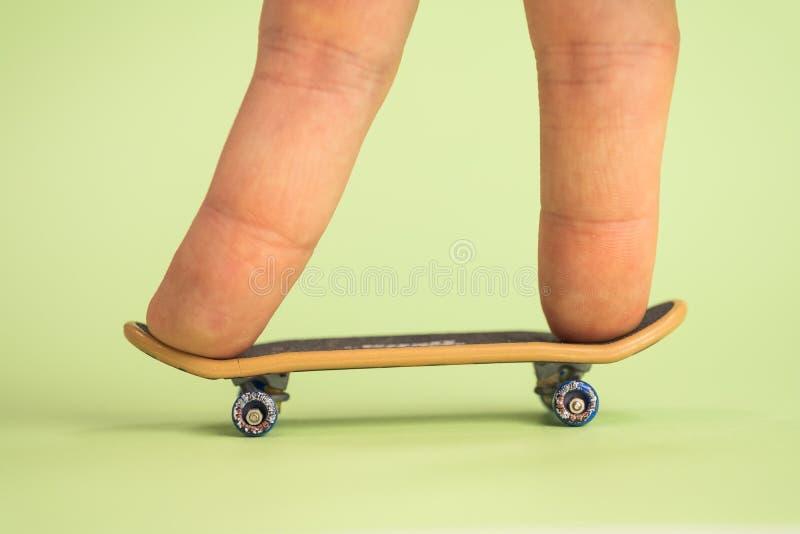 fingerboard Mann, der durch das kleine Skateboard mit zwei Fingern auf gr?nem Hintergrund hoplding ist lizenzfreies stockfoto
