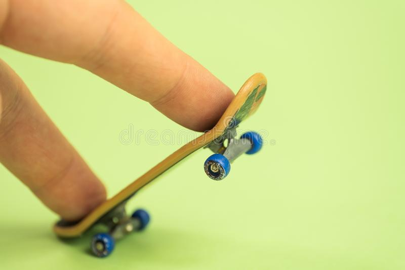 fingerboard Mann, der durch zwei Finger mit kleinem Skateboard auf grünem Hintergrund spielt stockfotografie