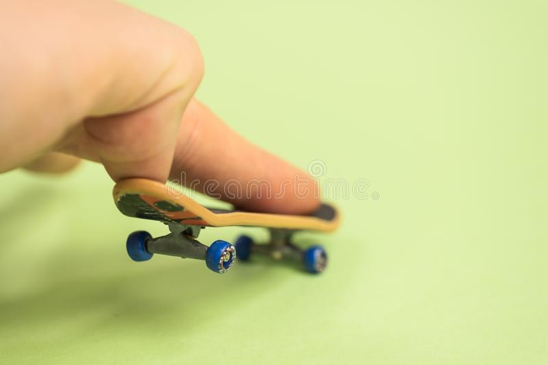 fingerboard Mann machen Trick durch zwei Finger mit kleinem Skateboard auf grünem Hintergrund lizenzfreies stockbild