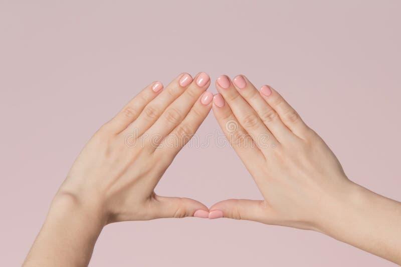Fingeres de la mujer con los clavos rosados imagen de archivo