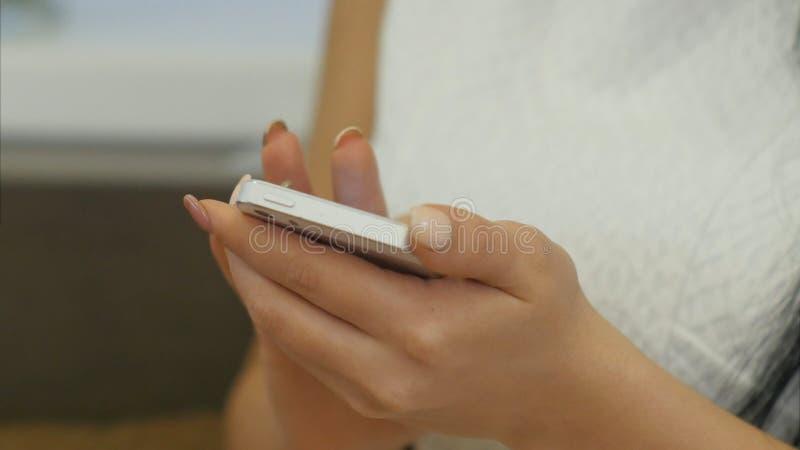 Fingeres de la mujer que mandan un SMS a mensajes usando el teléfono celular fotos de archivo