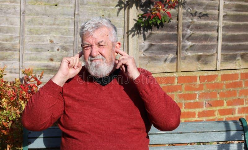 Fingeres del hombre mayor en sus oídos ruido foto de archivo