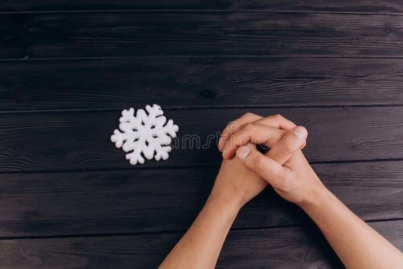 Fingeres entrelazados, manos masculinas blancas entrelazadas en cierre de madera r?stico negro de la tabla para arriba Visi?n sup fotografía de archivo libre de regalías