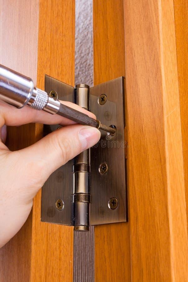 Fingeres masculinos con la bisagra que atornilla del destornillador en una puerta imágenes de archivo libres de regalías