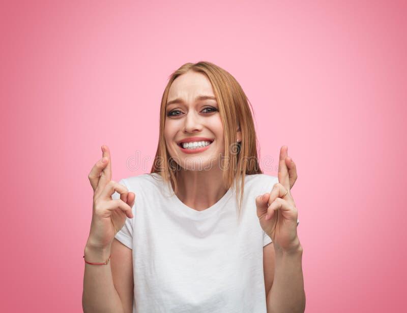 Fingeres que cruzan de la mujer esperanzada para la suerte fotos de archivo libres de regalías
