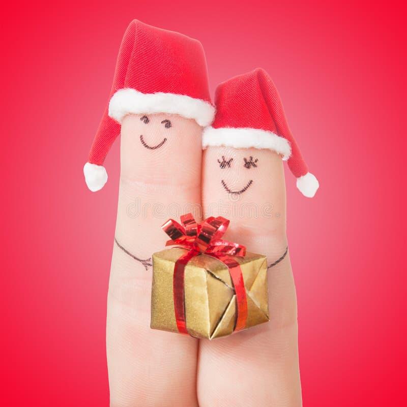 Fingergesichter in Sankt-Hüten mit Geschenkbox Glückliche Paare lizenzfreies stockfoto