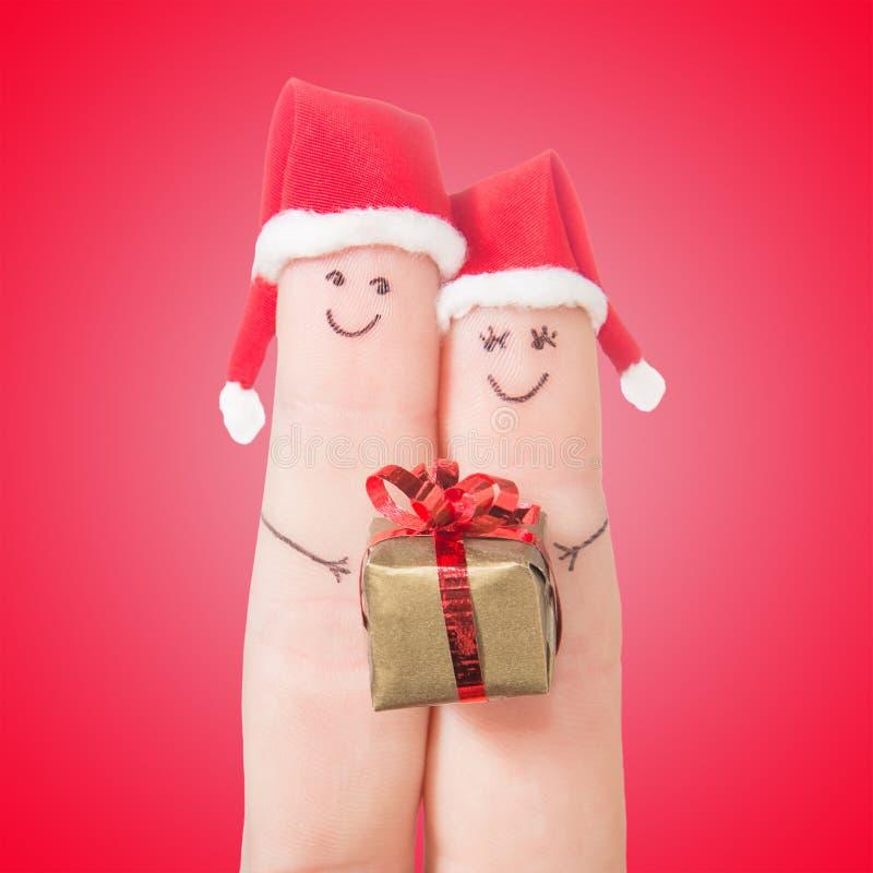 Fingergesichter in Sankt-Hüten mit Geschenkbox Glückliche Paare lizenzfreie stockfotos