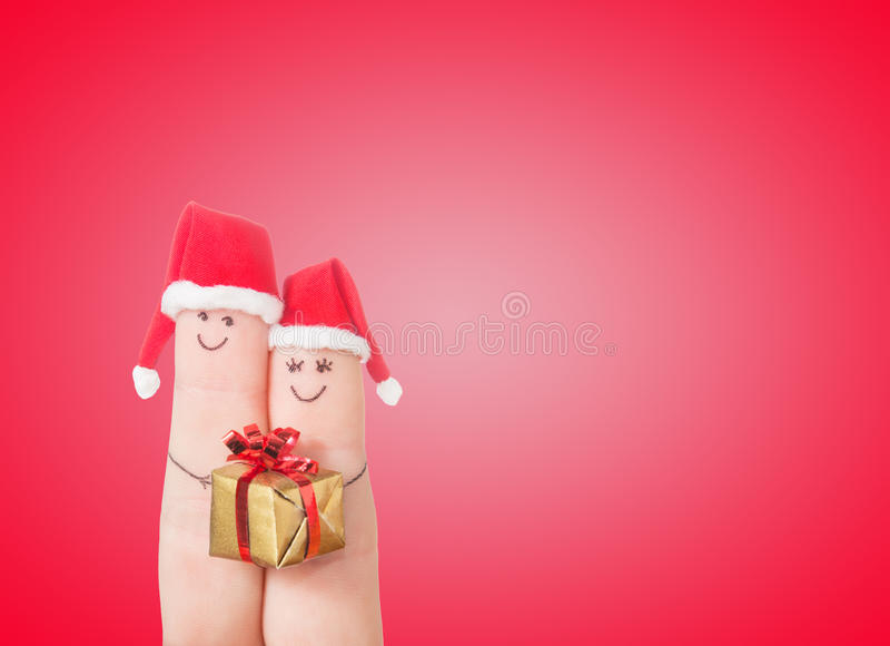 Fingergesichter in Sankt-Hüten mit Geschenkbox Glückliche Paare stockfotos