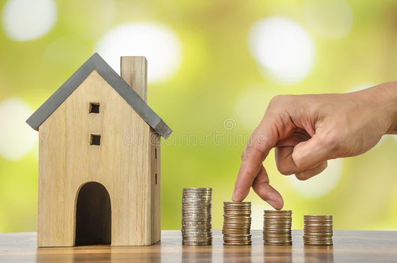 Fingerhandmoment framåtriktat på bunt av mynt och modellhus på växande idé för vit för utrymmebakgrundsbegrepp finans för affär arkivfoto