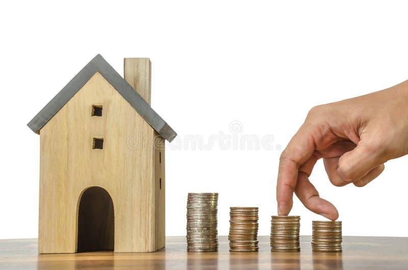 Fingerhandmoment framåtriktat på bunt av mynt och modellhus på växande idé för vit för utrymmebakgrundsbegrepp finans för affär arkivbilder
