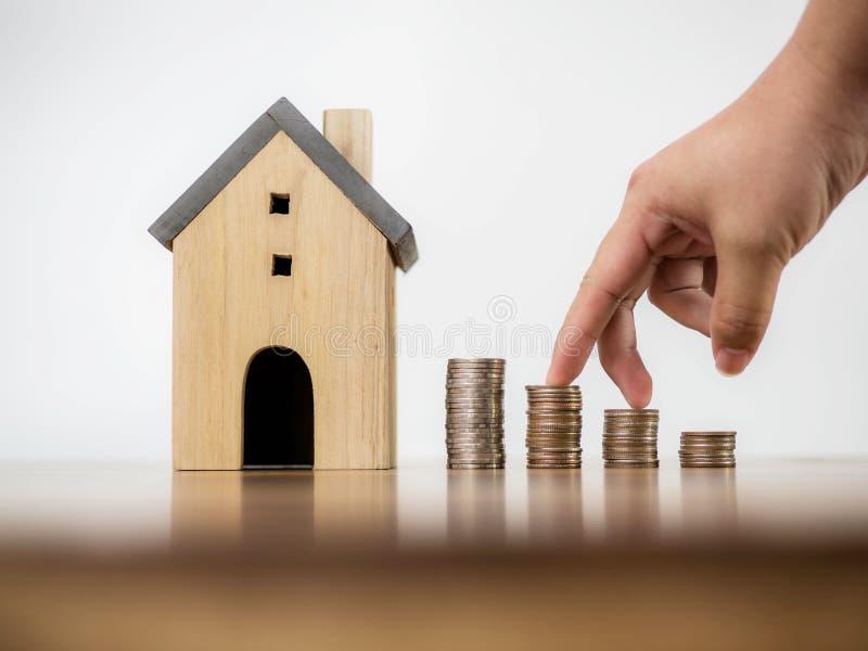 Fingerhandmoment framåtriktat på bunt av mynt och modellhus på växande idé för vit för utrymmebakgrundsbegrepp finans för affär royaltyfri foto
