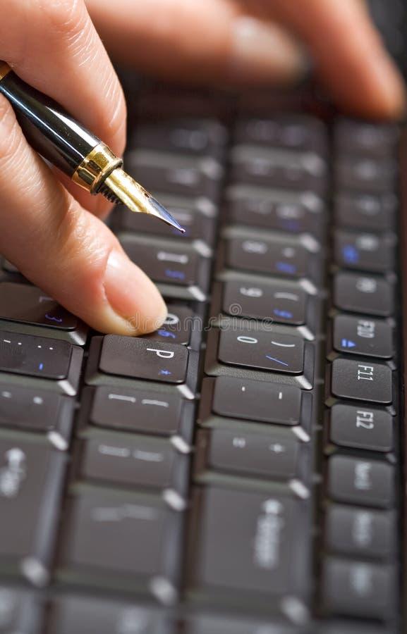 Fingerholdingfeder über Tastatur lizenzfreie stockfotos