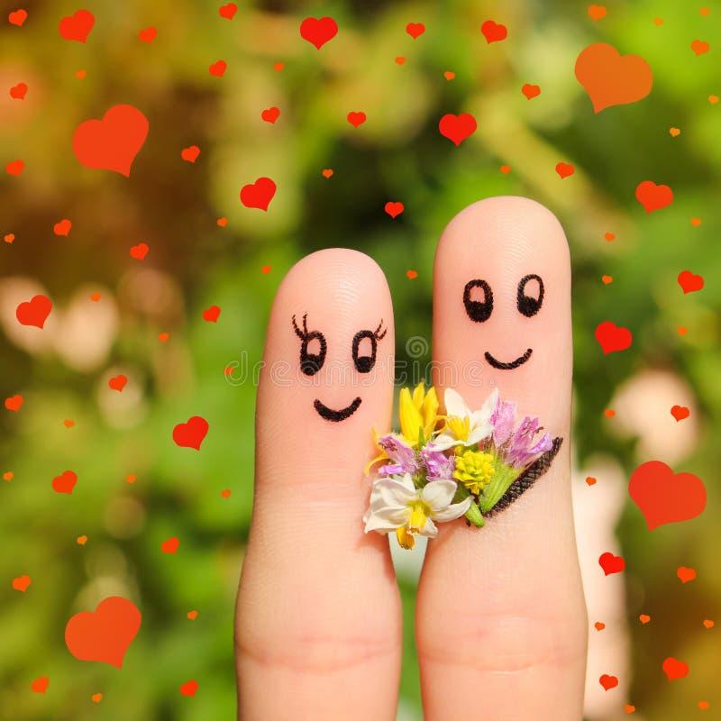 Fingerkonst av ett lyckligt par Mannen ger blommor till en kvinna royaltyfri bild