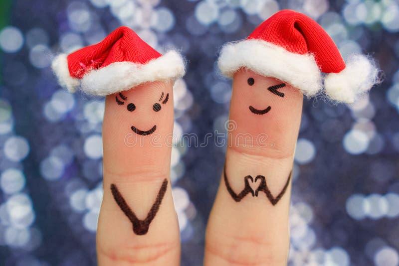Fingerkunst von Paaren feiert Weihnachten Konzept des Mannes und der Frau, die in den Hüten des neuen Jahres lachen stockbild
