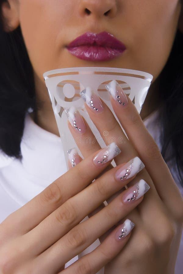Fingernails. Beautiful female fingernails holding a glass, cosmetics stock photo