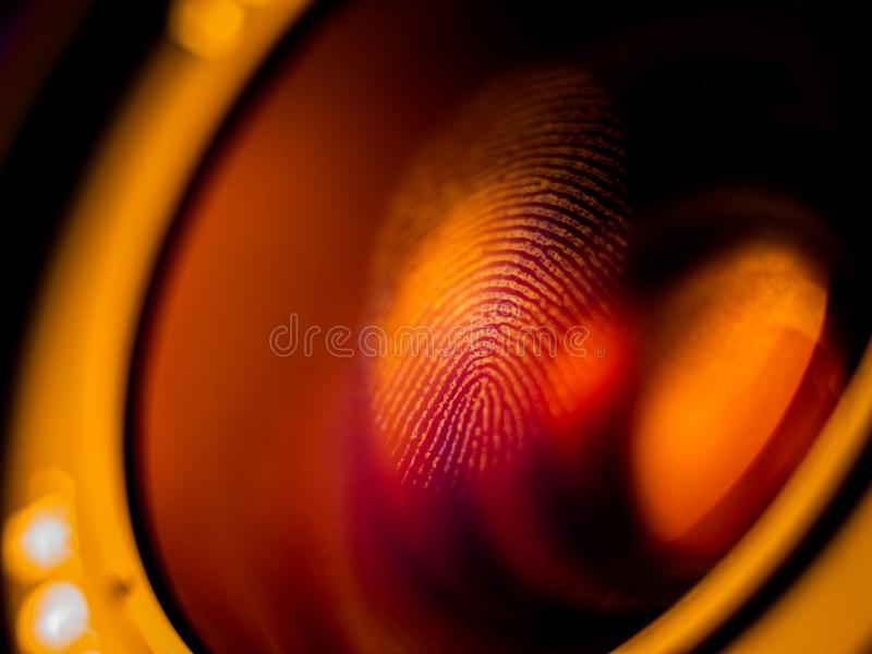Fingerprint macro on a lens. In red light, shallow depth of field. Biometric and security concept stock photos