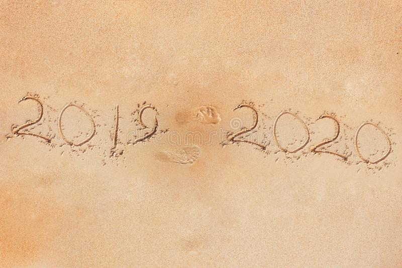 Fingerprint on a sandy beach 2019 and foot prints. The outgoing 2019 year. Concept royalty free stock photography