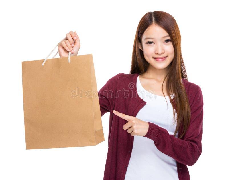 Fingerpunkt der jungen Frau zur Einkaufstasche lizenzfreie stockbilder